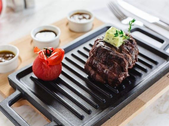 Steak and tomato on grill