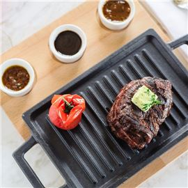 Steak on grill with sauces